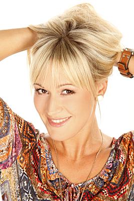 Portraitfoto einer jungen, blonden Frau, die in die Kamera lächelt und dabei ihre Haare nach oben aufgerafft hält.