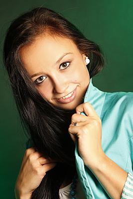 Portraitfoto einer jungen, brünetten Frau in einer grünen Bluse, die lächelnd in die Kamera schaut und den Kragen ihrer Bluse Richtung Kinn zieht.
