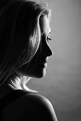 Schwarz-weißes Portraitfoto einer jungen Frau im Profil, deren blondes Haar ein Auge verdeckt und die mit halb geschlossenem Auge Richtung Boden blickt.
