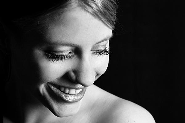 Schwarz-weißes Portraitfoto einer nackten, jungen Frau im Profil, die mit halb geschlossenen Augen Richtung Boden blickt und dabei freundlich lächelt.