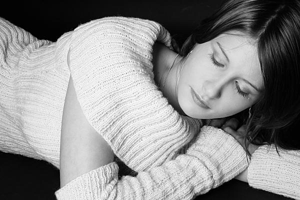 Schwarz-weißes Portraitfoto einer jungen, dunkelhaarigen Frau, die in einem weißen Wollpullover mit großem Kragen auf dem Bauch liegt und ihr Gesicht auf ihrer And ablegt.