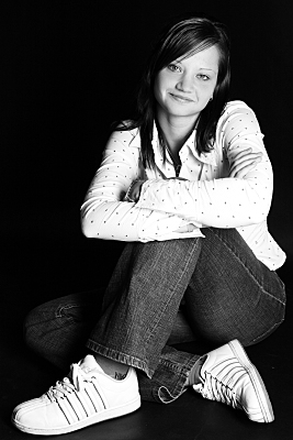 Schwarz-weißes Portraitfoto einer jungen, dunkelhaarigen Frau in einer hellen gepunkteten Bluse, die ihre Arme vor der Brust verschränkt.