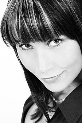 Schwarz-weißes Portraitfoto einer jungen, dunkelhaarigen Frau mit hellen Strähnchen, die auffordernd in die Kamera blickt.