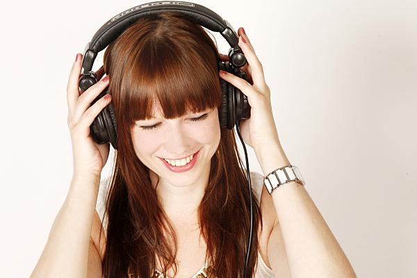 Portraitfoto einer jungen, brünetten Frau mit Kopfhörern auf den Ohren, die sie mit beiden Händen festhält und dabei glücklich lächelt.