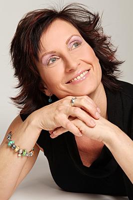 Portraitfoto einer Frau mit brünetten, kurzen Haaren, die lächelnd ihren Kopf auf die Hand stützt und verträumt nach oben schaut.