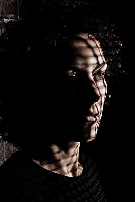 Portraitfoto einer jungen, dunkelhaarigen Frau mit Schattenspiel auf dem Gesicht vor einem dunklen Hintergrund.