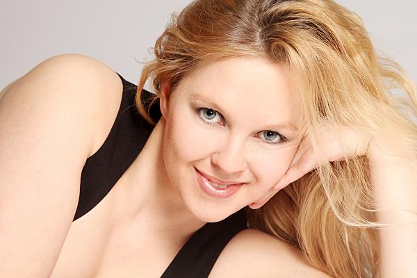 Portraitfoto einer auf der Seite liegenden jungen, blonden Frau in einem dunklen Top, die verführerisch in die Kamera blickt und dabei ihren Kopf auf dem aufgestellten Arm ablegt.