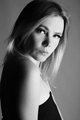 Schwarz-weißes Portraitfoto einer jungen Frau mit langen blonden Haaren, die verführerisch über ihre nackte Schulter hinweg Richtung Kamera blickt.