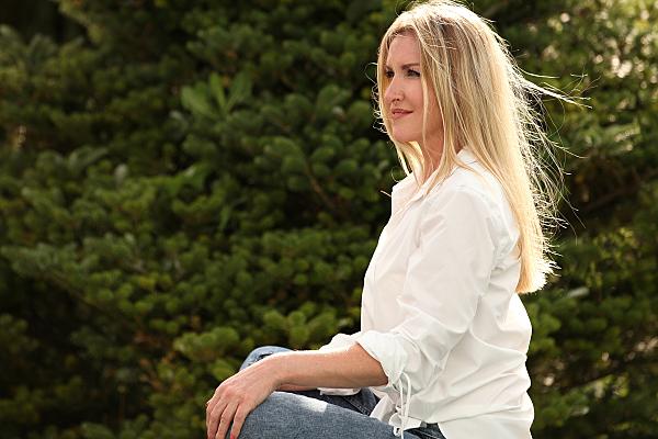 Portraitfoto einer jungen Frau mit langen blonden Haaren, Jeans und weißer Bluse, die im Schneidersitz vor einer Blätterkulisse sitzt und ihre Hände auf den Knien ablegt.