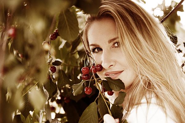 Portraitfoto einer jungen Frau mit langen, blonden Haaren zwischen Bäumen, die sich eine Blume vors Gesicht hält.