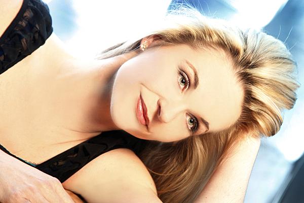 Portraitfoto einer auf der Seite liegenden jungen, blonden Frau in einem dunklen Top vor einem weiß-blauen Hintergrund, die lächelnd in die Ferne schaut und dabei ihren Kopf auf dem aufgestellten Arm