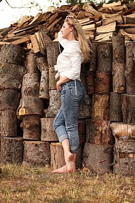Portraitfoto einer jungen Frau mit langen, blonden Haaren in weißer Bluse und Jeans im Profil vor mehreren Baumstämmen.