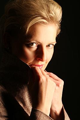 Portraitfoto einer blonden Frau vor schwarzem Hintergrund.