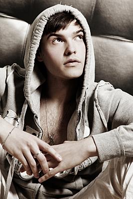 High-Key Portrait eines junges Mannes mit Kapuzenjacke, vor einer Couch auf dem Boden sitzend, der mit aufgesetzter Kapuze nach links oben von der Kamera weg schaut.