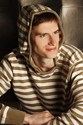 Kopfportrait eines jungen Mannes mit gestreifter Jacke und aufgesetzter Kapuze lächelnd an der Kamera vorbeischaut.