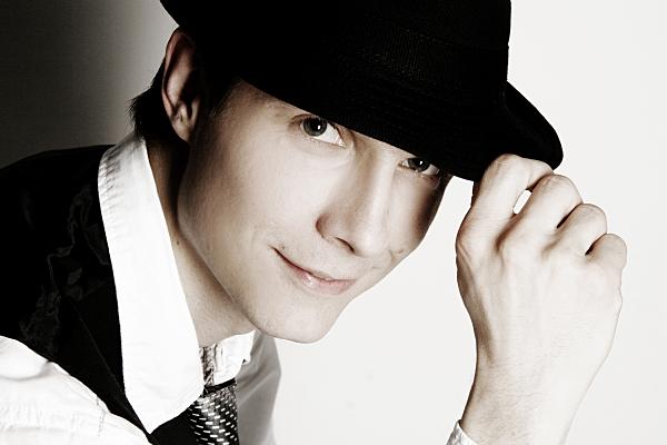 Schwarz-weiß Portrait eines Mannes mit weißem Hemd, schwarzer Weste und Hut, der unter der Krempe hervor in die Kamera blickt und diese mit einer Hand berührt.