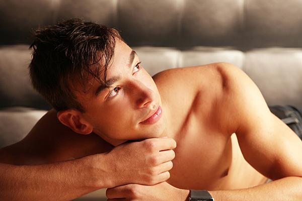 Portrait eines jungen Mannes, im Legen aufgenommen, der sein Kinn auf seinen Händen abstützt und nach links oben ins Richtung Licht schaut.