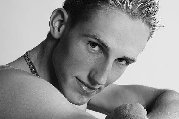 Seitliches Portrait eines jungen Mannes, der über seine rechte, nackte Schulter in die Kamera schaut.