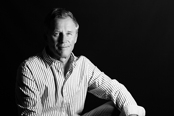 Low-Key Portrait eines Mannes, der seitlich sitzend neutral in die Kamera blickt.