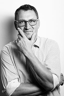Schwarz-weißes Portrait eines Mannes, der mit seiner Hand am Kinn in Denkerpose in die neutral in die Kamera schaut.