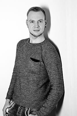 Schwarz-weißes Portrait eines Mannes, der stehend an einer Wand lehnend in die Kamera blickt.