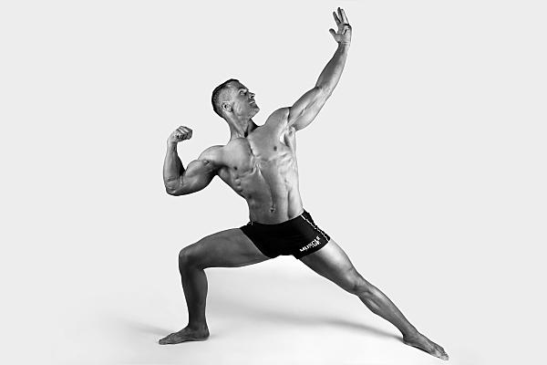 Sportfoto eines muskulösen Mannes mit nacktem Oberkörper und schwarzer Boxershorts, der in Kriegerposition steht und nach oben schaut.