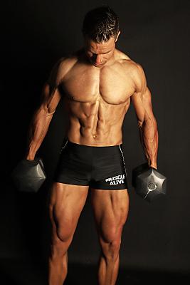Sportfoto eines muskulösen Mannes mit nacktem Oberkörper und dunkler Sporthose vor einem schwarzen Hintergrund, der seine Arme nach unten hält und nach unten schaut.