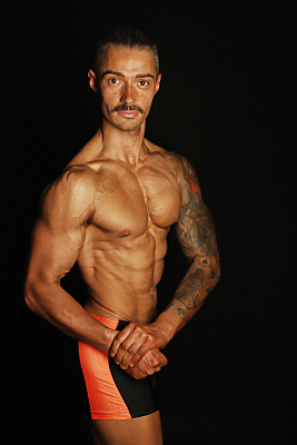 Sportfoto eines muskulösen Mannes mit Schnurrbart und nacktem Ooberkörper vor einem schwarzen Hintergrund, der seine Arme angewinkelt vor seiner Taille hält und nach unten schaut.