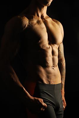 Sportfoto eines muskulösen, nackten Männeroberkörpers vor einem schwarzen Hintergrund, der seine Arme angewinkelt über den Kopf hält und nach unten schaut.