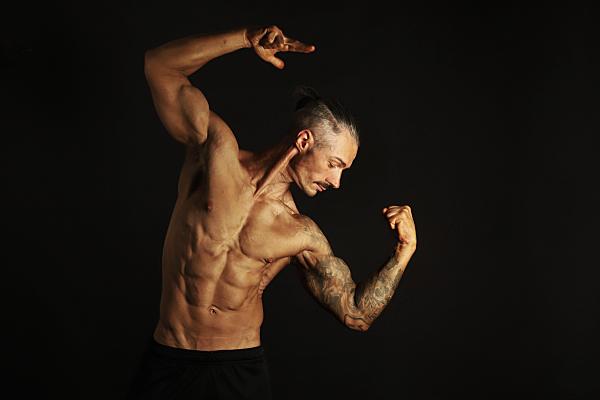 Sportfoto eines muskulösen Mannes mit nacktem Oberkörper und dunkler Sporthose vor einem schwarzen Hintergrund, der seine Arme angewinkelt über den Kopf hält und nach unten schaut.