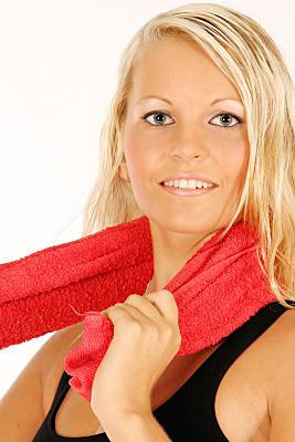 Sportfoto einer jungen, blonden Frau im schwarzen Top, die ein rotes Handtuch um den Nacken geschlungen hält.