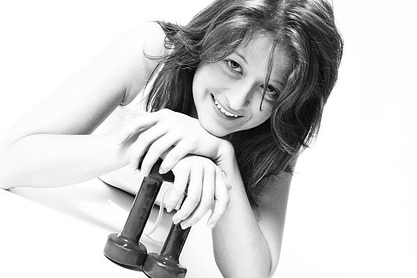 Schwarz-weißes Sportfoto einer auf den Bauch liegenden, dunkelhaarigen Frau in weißem Top, die ihre Hände auf zwei kleine Hanteln stützt.
