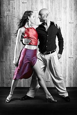 Sportfoto eines umschlungenen Tanzpaares. Die Tänzerin trägt ein rotes, bauchfreies Top und einen lila, beinausgestellten Rock. Der Tänzer trägt ein dunkles Hemd und eine helle Hose.