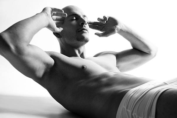Sportfoto eines muskulösen Mannes mit nacktem Oberkörper und in weißer Boxershorts, der die Hände an den Kopf hält und seine Bauchmuskeln beim Sit-up trainiert.