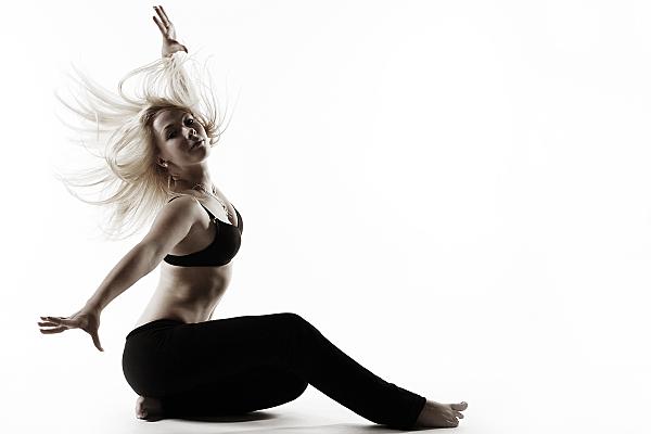 Schwarz-weißes Sportfoto einer sitzenden rau mit schwarzem, bauchfreien Top und dunkler Sporthose, deren blonde Haare wehen und die ihre Arme ausstreckt.