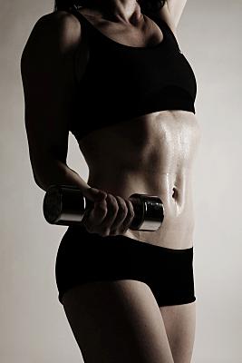 Sportfoto eines durchtrainierten Frauenoberkörpers mit dunklem, bauchfreien Top und angewinkelten Armen.