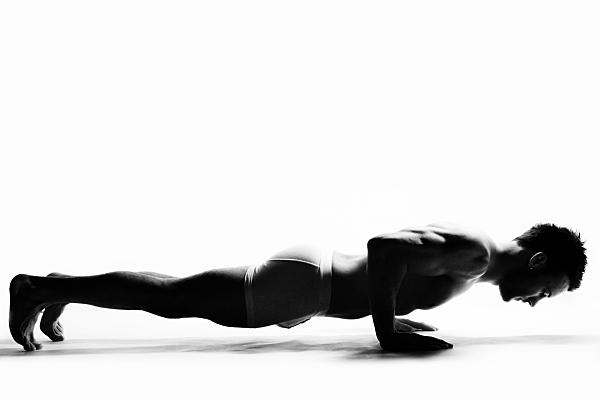 Schwarz-weißes Sportfoto eines muskulösen Mannes, der sich auf seinen Händen in den Liegestütz drückt und nach unten schaut.