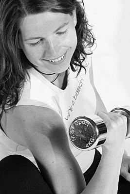 Schwarz-weiß Sportfoto einer durchtrainierten Frau mit weißem Top, die eine Kurzhantel festhaltend, ihren Bizeps anspannt und nach unten schaut.