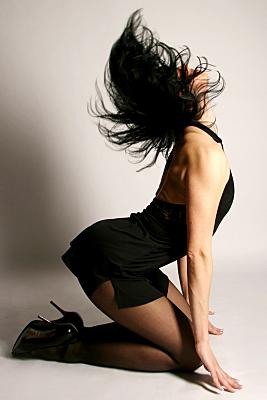 Sportfoto einer schlanken Frau mit nach hinten geworfenem, dunklen Haar in einem schwarzen Neckholder-Kleid und mit schwarzen High-Heels.