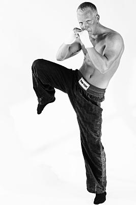 Sportfoto eines muskulösen Mannes mit nacktem Oberkörper und in schwarzer Sporthose, der die angewinkelten, in Bandagen gehüllten Hände in Boxpose hält und ein Knie nach oben gezogen hält.