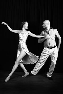 Schwarz-weißes Sportfoto eines tanzenden Paares. Die Tänzerin trägt ein helles, schwingendes Kleid mit Beinausschnitt. Der Tänzer ein helles Hemd sowie eine Hose mit dunklem Gürtel.