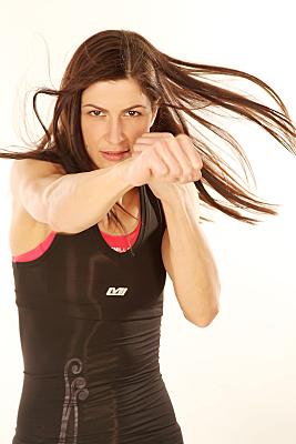 Sportfoto einer durchtrainierten Frau mit wehendem, langen dunklen Haar und schwarzem Sporttop, die eine Hand mit geballter Faust ans Kinn hält, während sie die andere zum Schlag bereit nach vorne rec