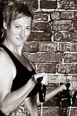 Sportfoto einer durchtrainierten Frau in schwarzem, bauchfreien Oberteil, die mit beiden Händen Sportgeräte nach oben zieht und herausfordernd in die Kamera schaut.