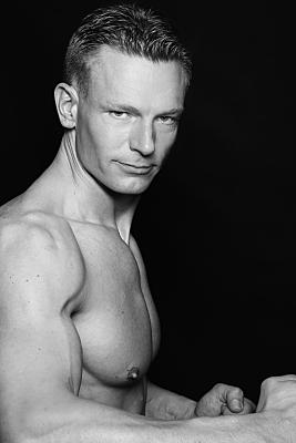 Sportfoto eines muskulösen Mannes mit nacktem Oberkörper, der im Profil seine Arme anwinkelt, die Fäuste ballt und herausfordernd in die Kamera schaut.