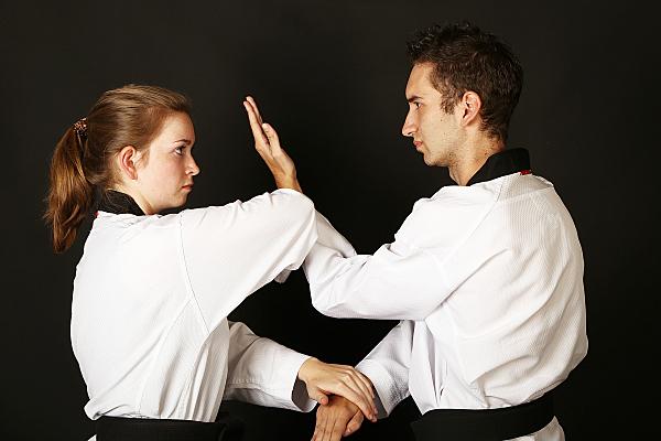 Sportfoto zweier Karate-Kämpfer in Kampfposition und in weißen Karateanzügen.
