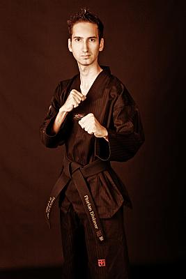Sportfoto eines dunkjelhaarigen Mannes mit schwarzem Karate-Outfit und in kampfbereiter Pose.