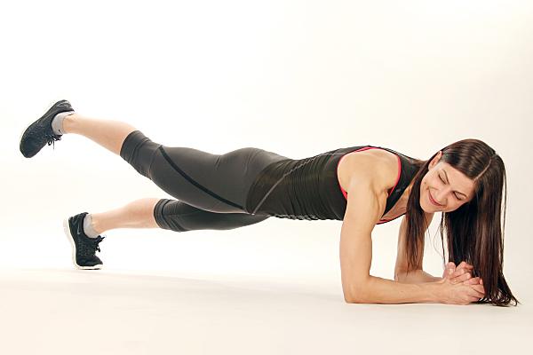 Sportfoto einer schlanken, dunkelhaarigen Frau mit dunkler Sporthose und Top, die sich auf ihre Unterarme stützt und dabei lächelnd ein Bein in die Luft reckt.
