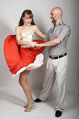 Sportfoto eines tanzenden Paares. Die Tänzerin trägt einen wirbelnden, roten Rock und ein geblümtes Oberteil, der Mann ein graues Hemd und eine helle Hose mit dunklem Gürtel.