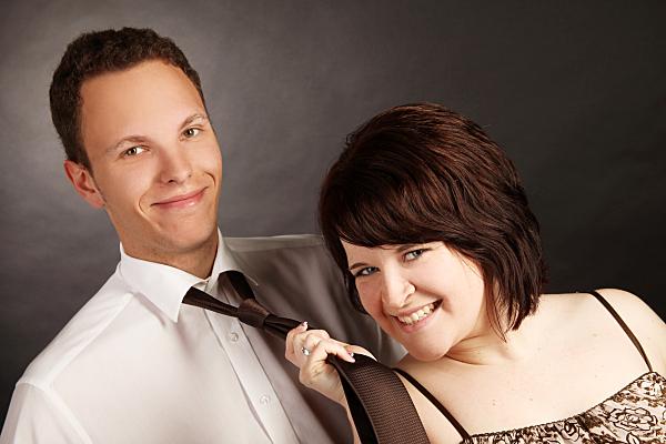 Schräges Portrait eines Paares vor dunklem Hintergrund, auf dem die Frau den Mann an der Krawatte hält und beide in die Kamera lächeln.
