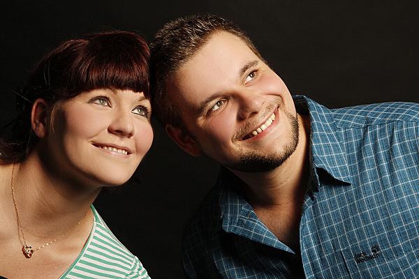 Nahportrait eines Paares vor dunklem Hintergrund, welches die Köpfe zueinander hält und an der Kamera vorbei in die Ferne lächelt.